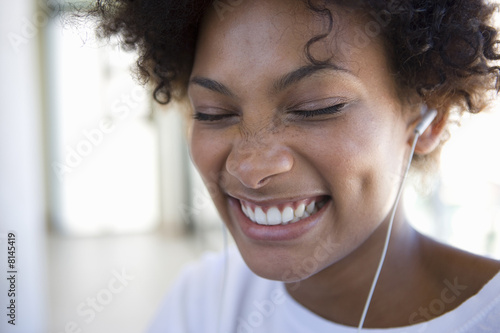 Young woman wearing earphones, smiling, close-up