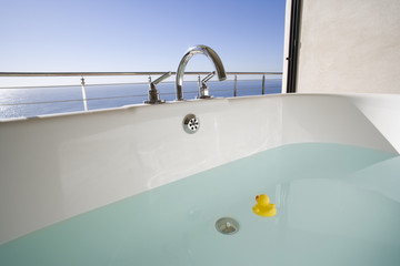 Bath with rubber duck on balcony by sea