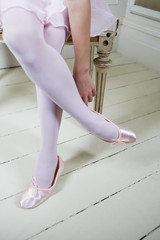 Young girl putting on her ballet shoes