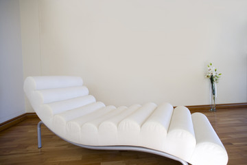 White chaise longue on wooden floor