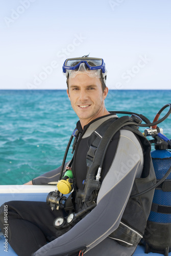 A man sitting on a boat about to go scuba diving