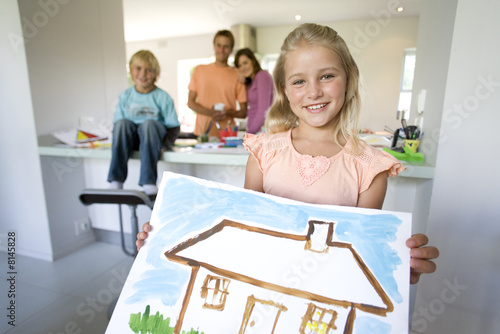 Girl(6-8) holding painting of house, smiling, portrait, family in background