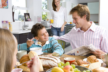 Family having breakfast at kitchen table, mother standing in background