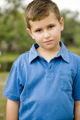 boy standing in park wearing blue polo shirt