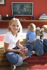 Boy and girl (6-8) on rug in front of television, portrait of girl smiling and using mp3 player
