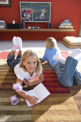 Boy and girl (6-8) on rug in front of television, portrait of girl smiling with book and mp3 player, elevated view