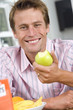 Man holding up green apple, smiling, portrait, close-up