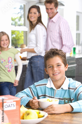 Boy (6-8) eating breakfast at table, smiling, portrait, family in background