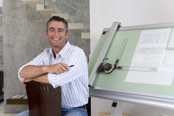 Man sitting by drafting board, smiling, portrait