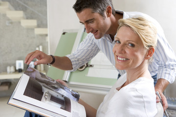 Couple with magazine by drafting board, portrait of woman smiling