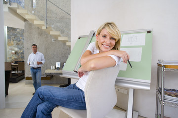 Woman sitting by blue prints on drafting board in home office, smiling portrait, man standing in background