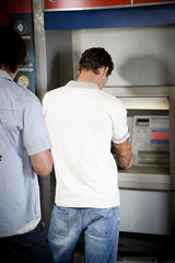 Young man using a cashpoint or ATM