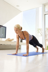 Mature woman doing push-ups on exercise mat in living room