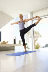 Mature woman in yoga stance on exercise mat in living room, low angle view
