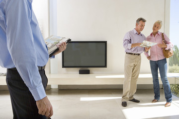 Male real estate agent and mature couple standing in living room, couple in background