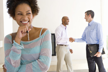 Woman holding house keys, smiling, male real estate agent and man shaking hands in background