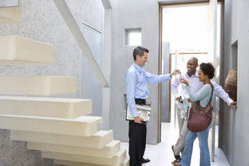 Male real estate agent handing keys to couple, standing by stairs, smiling, side view