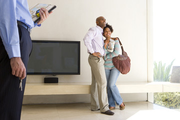Couple embracing in living room, male real estate agent standing in foreground