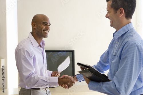 Man and male real estate agent shaking hands in living room, smiling, side view