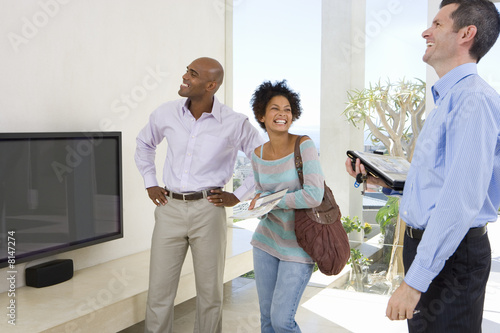 Couple standing in living room by male real estate agent, smiling