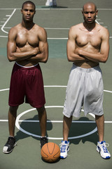 Two Young African American standing side by side on an urban basketball court