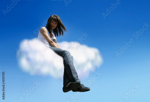 Beautiful young woman sitting on white cloud