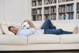 Man hugging ball asleep on sofa by bookshelf, low angle view