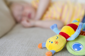Baby girl (12-15 months) asleep on sofa, toys in foreground (differential focus)