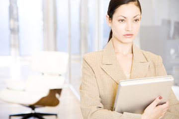 Businesswoman looking serious whilst clutching her laptop