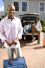 Man with suitcase in driveway, family by car in background, smiling, portrait