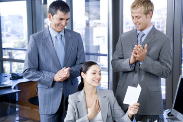 Two male colleagues congratulating a female colleague