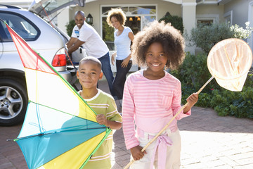 Girl (8-10) with fishing net by brother (6-8) with kite in driveway, smiling, portrait