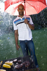 Man sheltering from rain under umbrella by barbeque, portrait