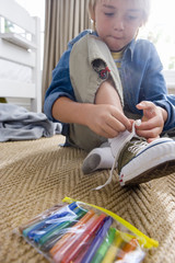 Boy (6-8) tying shoelace in bedroom, low angle view