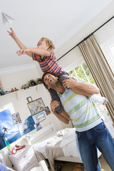 Son (6-8) on father's shoulders, playing with paper dart (tilt)