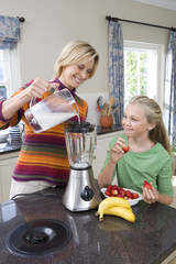 Mother and daughter (8-10) making banana and strawberry smoothie, smiling