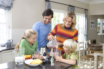 Family of four making fruit smoothies in kitchen, smiling