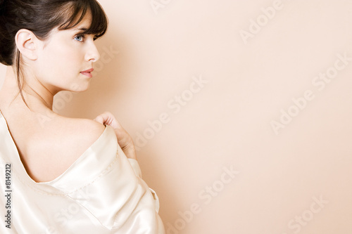 Elegant young woman in a white silk dress or wrap