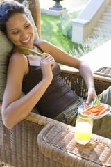 Young woman with plate of vegetable sticks in armchair outdoors, smiling, elevated view