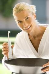 Woman in bathrobe with electric toothbrush, smiling, portrait