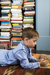 boy looking at picture book on the floor