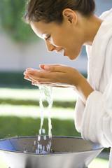 Young woman in bathrobe washing face, profile