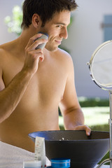 Bare chested man using electric razor, looking in mirror, smiling, close-up