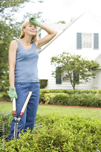 woman with wiping brow holding shears
