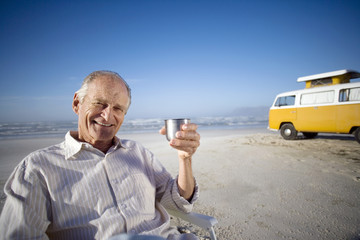 Senior man drinking from insulated flask on beach by camper van, smiling, portrait