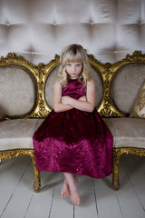 Young girl in a party dress looking bored and unhappy