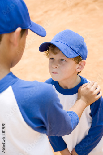 older boy talking down to younger boy at baseball practice