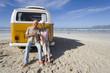 Senior couple sitting on back of camper van on beach, smiling, portrait