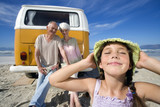 Girl (7-9) holding hat on head on beach by grandparents on back of camper van, smiling, close-up