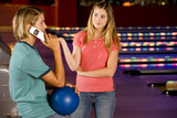 Teenage boy and girl in a bowling alley, boy talking on mobile phone